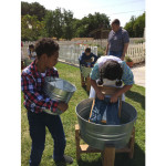 Students washing clothes with washboard, dumping water