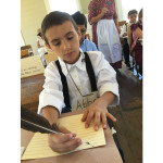 Student writing with quill pen and ink