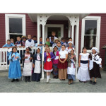 Students in front of one-room schoolhouse with School Marm