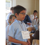 Student stands at desk in Schoolhouse